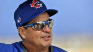 Toronto Blue Jays manager Charlie Montoyo waits for the start of a bullpen session during workouts at the team's spring training facilities in Dunedin, Fla., on February 14, 2020. With a few days of summer training camp workouts under his players' belts, Blue Jays manager Charlie Montoyo was scheduled to hold a conference call Wednesday afternoon to discuss his team's preparation for the upcoming 60-game regular season. THE CANADIAN PRESS/Steve Nesius