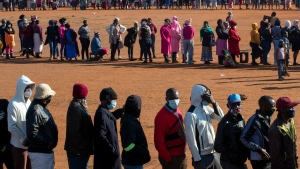FILE — In this May 20, 2020 file photo, people affected by the coronavirus economic downturn line up to receive food parcels in Pretoria, South Africa. (AP Photo/Themba Hadebe/File)