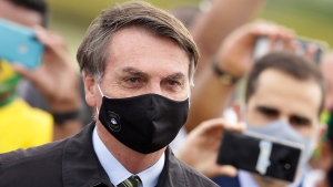 In this May 25, 2020, file photo, Brazil's President Jair Bolsonaro, wearing a face mask amid the coronavirus pandemic, stands among supporters as he leaves his official residence of Alvorada palace in Brasilia, Brazil. Bolsonaro said Tuesday, July 7, he tested positive for COVID-19 after months of downplaying the virus's severity while deaths mounted rapidly inside the country. (AP Photo/Eraldo Peres, File)