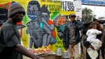 """People walk past an informational mural warning people about the dangers of the new coronavirus and how to prevent transmission, with words in Swahili reading """"We are the Cure"""", painted by youth artists from the Uweza Foundation, in the Kibera slum, or informal settlement, of Nairobi, Kenya Wednesday, July 8, 2020. Africa now has more than a half-million confirmed coronavirus cases, according to the Africa Centers for Disease Control and Prevention, but the true number of cases among Africa's 1.3 billion people is unknown as its 54 countries face a serious shortage of testing materials for the virus. (AP Photo/Brian Inganga)"""