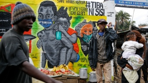 "People walk past an informational mural warning people about the dangers of the new coronavirus and how to prevent transmission, with words in Swahili reading ""We are the Cure"", painted by youth artists from the Uweza Foundation, in the Kibera slum, or informal settlement, of Nairobi, Kenya Wednesday, July 8, 2020. Africa now has more than a half-million confirmed coronavirus cases, according to the Africa Centers for Disease Control and Prevention, but the true number of cases among Africa's 1.3 billion people is unknown as its 54 countries face a serious shortage of testing materials for the virus. (AP Photo/Brian Inganga)"