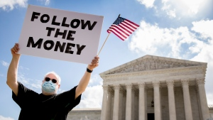 "Bill Christeson holds up a sign that reads ""Follow the Money"" outside the Supreme Court, Thursday, July 9, 2020, in Washington. (AP Photo/Andrew Harnik)"