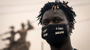 "A protester wears a mask to curb the spread of the coronavirus on which is written ""I can't breathe"", referring to words spoken by George Floyd before his death, at a demonstration against his killing by police officers in Minneapolis, USA, held in front of the African Renaissance Monument in Dakar, Senegal Saturday, June 6, 2020. His death has led to Black Lives Matter protests in many countries and across the US. (AP Photo/Sylvain Cherkaoui)"