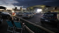 """People attend a drive-in movie screening of the film """"Yesterday,"""" Wednesday, July 8, 2020, in a parking lot behind the Boston Convention and Exhibition Center, in Boston. A Toronto concert organizer says confusing guidelines for Ontario drive-ins have left him little choice but to postpone a major weekend event meant to unite friends and families in their cars.THE CANADIAN PRESS/AP/Steven Senne"""