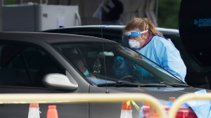 A health care worker prepares to test a driver in line at a drive-thru COVID-19 testing site outside Hard Rock Stadium, Wednesday, July 8, 2020, in Miami Gardens, Fla. Florida is one of the nation's hot spots for the coronavirus. (AP Photo/Wilfredo Lee)
