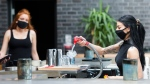 Bartender Alicia Mattoe, right, makes a drink as patrons sit on the patio at Joey Sherway, part of the Joey Restaurant chain during the COVID-19 pandemic in Toronto. (Photo: The Canadian Press/Nathan Denette)