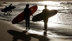 FILE - In this April 28, 2020, photo, surfers walk the beach in Sydney, Australia. (AP Photo/Rick Rycroft, File)