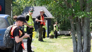 Police officers and volunteers stand in line before entering the woods to search, Friday, July 10, 2020 in Saint-Apollinaire Que. Police are continuing their search around a Quebec City suburb after they issued an Amber Alert Thursday for two young girls and their 44-year-old father who investigators believe disappeared following a highway car crash.THE CANADIAN PRESS/Jacques Boissinot