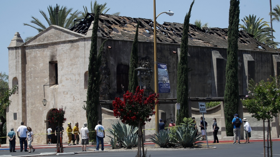 Curious onlookers stand outside the San Gabriel Mission in the aftermath of a morning fire Saturday, July 11, 2020, in San Gabriel, Calif. The fire destroyed the rooftop and most of the interior of the 249-year-old church that was undergoing renovation. (AP Photo/Marcio Jose Sanchez)