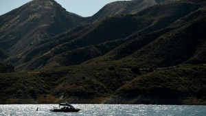 "A search-and-rescue boat continues looking for missing actress Naya Rivera at Lake Piru, Friday, July 10, 2020, in Los Padres National Forest, Calif., about 55 miles (90 kilometers) northwest of Los Angeles. Authorities said that they believe the ""Glee"" star drowned in the lake Wednesday, but they are continuing the search for her two days after her 4-year-old son was found alone in a rented boat. (AP Photo/Chris Pizzello)"