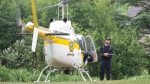A police officer stands by the helicopter as they search on Saturday, July 11, 2020 in Saint-Apollinaire, Quebec. Quebec provincial police say two girls who were the subject of an Amber Alert have been found dead. THE CANADIAN PRESS/Jacques Boissinot
