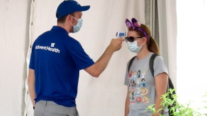 A guests gets her temperature taken before entering the official reopening day of the Magic Kingdom at Walt Disney World in Lake Buena Vista, Fla., Saturday, July 11, 2020. Disney reopened two Florida parks, the Magic Kingdom and Animal Kingdom, Saturday with limited capacity and safety protocols in place in response to the coronavirus pandemic. (Joe Burbank/Orlando Sentinel via AP)