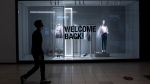 A shopper passes a store's display welcoming back patrons at the Bayshore Shopping Centre mall in Ottawa, on its first day open as part of Stage 2 of Ontario's plan to lift lockdowns implemented in response to the COVID-19 pandemic, on Friday, June 12, 2020. THE CANADIAN PRESS/Justin Tang