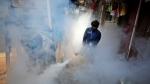 A worker fumigates a slum to prevent an outbreak of dengue fever in Jakarta, Indonesia, Wednesday, April 22, 2020. While 2019 was the worst year on record for global dengue cases, experts fear an even bigger surge is possible because their efforts to combat it were hampered by restrictions imposed in the coronavirus pandemic. (AP Photo/Dita Alangkara)