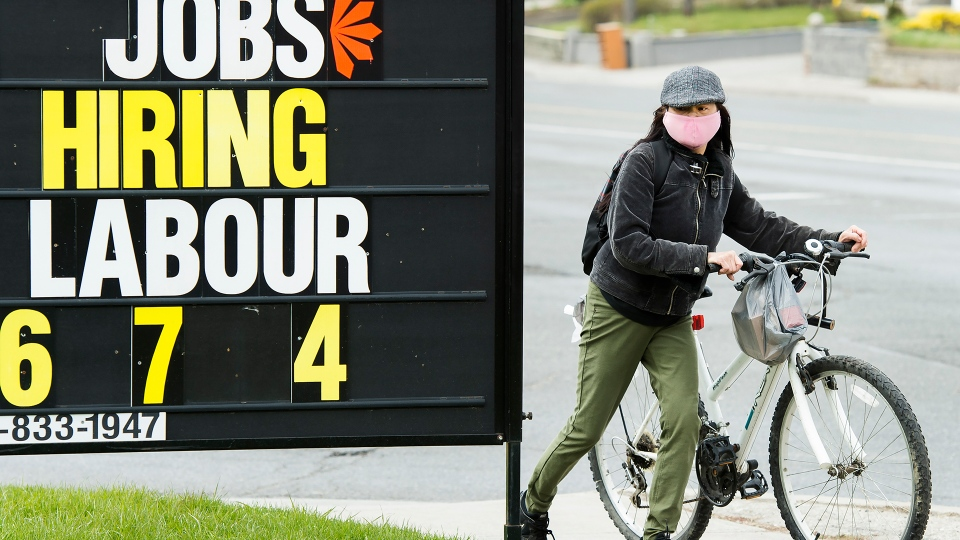 A woman checks out a jobs advertisement sign during the COVID-19 pandemic in Toronto on April 29, 2020. THE CANADIAN PRESS/Nathan Denette