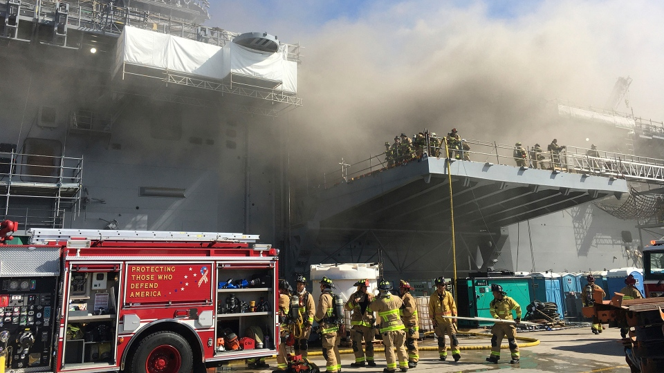 """In a photo provided by the U.S. Navy, sailors and Federal Fire San Diego firefighters work to extinguish a fire aboard the USS Bonhomme Richard on Sunday, July 12, 2020, at Naval Base San Diego. Twenty-one people suffered minor injuries in an explosion and fire Sunday on board a ship, military officials said. The blaze was reported shortly before 9 a.m., said Mike Raney, a spokesman for Naval Surface Force, U.S. Pacific Fleet. Seventeen sailors and four civilians were hospitalized with """"non-life threatening injuries,"""" Raney said in a brief statement. (Petty Officer 1st Class Jason Ko/U.S. Navy via AP)"""