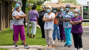 Workers watch as 150 nursing union members show support at Orchard Villa Long-Term Care in Pickering, Ontario on Monday June 1, 2020.  THE CANADIAN PRESS/Frank Gunn