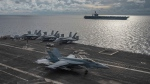 In this photo provided by U.S. Navy,  an F/A-18E Super Hornet lands on the flight deck of the USS Ronald Reagan (CVN 76), as USS Nimitz (CVN 68) steams alongside in the South China Sea, Monday, July 6, 2020. China on Monday, July 6, accused the U.S. of flexing its military muscles in the South China Sea by conducting joint exercises with two U.S. aircraft carrier groups in the strategic waterway.(Mass Communication Specialist 2nd Class Samantha Jetzer/U.S. Navy via AP)