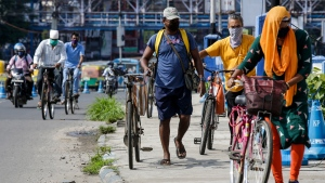 People wearing face masks cross a bridge with their cycles in Kolkata, India, Tuesday, July 14, 2020. Several Indian states imposed weekend curfews and locked down high-risk areas as the number of coronavirus cases surged past 900,000 on Tuesday. (AP Photo/Bikas Das)