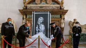 A recovered stolen artwork by British artist Banksy, that was painted as a tribute to the victims of the 2015 terror attacks at the Bataclan music hall in Paris, is unveiled during a ceremony at the French Embassy in Rome, Tuesday, July 14, 2020. (AP Photo/Domenico Stinellis)