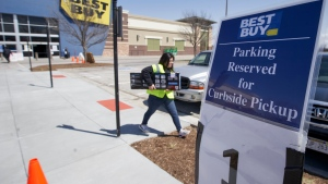 A Best Buy employee delivers an item to a waiting client in Omaha, Neb., Wednesday, April 15, 2020. Best Buy, the nation's largest consumer electronics chain, will require customers to wear face coverings at all of its stores nationwide, even in states or localities that don't require them to do so. The company said Tuesday, July 14, 2020 it will provide a face covering if a customer doesn't have one, and small children and those unable to wear one for health reasons may enter without one. (AP Photo/Nati Harnik)