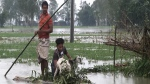 In this video grab taken from the Associated Press Television footage Bangladeshi men with a goat row a banana raft through flood waters in Lalmonirhat, Bangladesh, Monday, July 13, 2020. (AP Photo/Bayezid Ahmed)