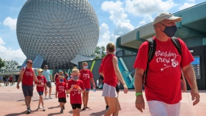 Guests arrive to attend the official re-opening day of Epcot at Walt Disney World in Lake Buena Vista, Fla., Wednesday, July 15, 2020. All four of Disney's Florida parks are now open, including Hollywood Studios, the Magic Kingdom and Animal Kingdom, with limited capacity and safety protocols in place in response to the coronavirus pandemic.(Joe Burbank/Orlando Sentinel via AP)
