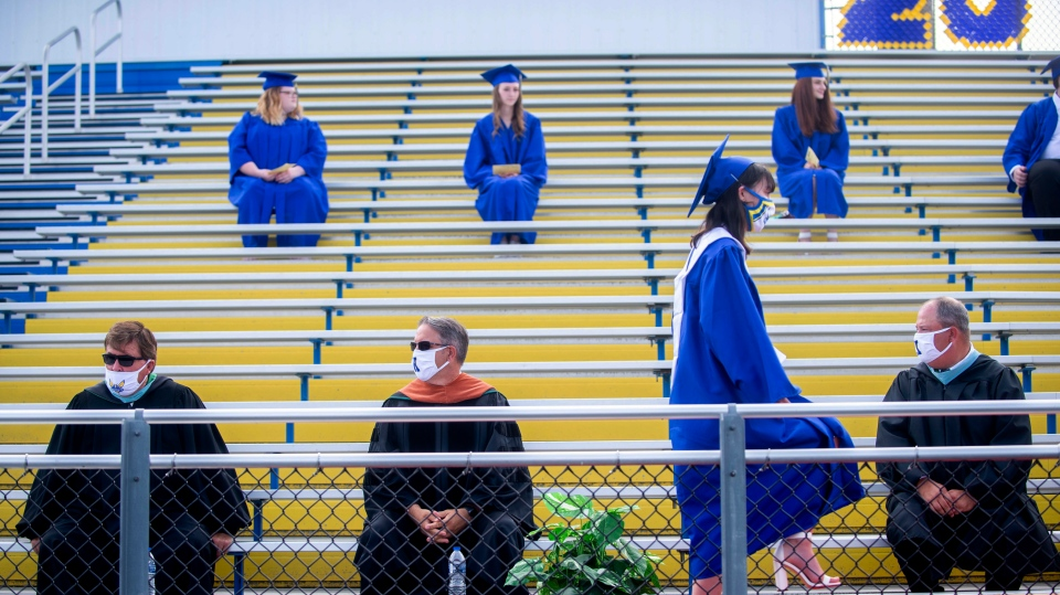 Valedictorian Ava Kelsey wears a mask as she walks up to receive her diploma as nearly 200 Kearsley High School graduates attend a commencement ceremony Wednesday, July 15, 2020, at the high school in Genesee Township, Mich. Kearsley Community Schools held four commencement ceremonies at the high school football field to keep the crowds small and adhere to social distancing guidelines amid the COVID-19 pandemic. (Jake May/The Flint Journal via AP)