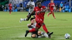 Toronto FC forward Ayo Akinola, front, scores his second goal of the game during the first half of an MLS soccer match against the Montreal Impact, Thursday, July 16, 2020, in Kissimmee, Fla. (AP Photo/John Raoux)