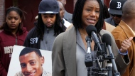"""FILE - In this April 21, 2011, file photo, Thulani DeMarsay, right, aunt of Danroy """"DJ"""" Henry Jr., who was shot and killed by a police officer, speaks as Henry's uncle Jamele Dozier, left, holds a photograph of Henry during a news conference in Boston's Roxbury neighborhood. Celebrities including Rihanna, Jay-Z and Charlize Theron have called for the U.S. Department of Justice in July 2020, to investigate the case of Henry, a black Pace University football player killed by a white police officer in New York after the team's homecoming game in October 2010. (AP Photo/Steven Senne, File)"""