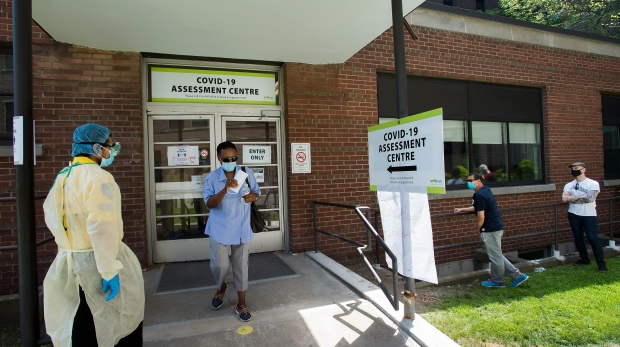A person leaves as other people line up to be tested at a COVID-19 assessment centre in Toronto on Tuesday, May 26, 2020. THE CANADIAN PRESS/Nathan Denette