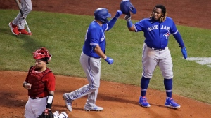 Toronto Blue Jays' Rowdy Tellez, center, is congratulated by Vladimir Guerrero Jr., right, after his two-run home run during the sixth inning of an exhibition baseball game against the Boston Red Sox, Tuesday, July 21, 2020, at Fenway Park in Boston. At left is Boston Red Sox catcher Christian Vazquez. (AP Photo/Charles Krupa)