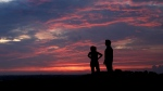 A couple watch the sunset from a park, Friday, July 3, 2020, in Kansas City, Mo. THE CANADIAN PRESS/AP-Charlie Riedel