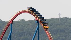 People wear face masks as they ride 'The Goliath', roller coaster at La Ronde amusement park in Montreal, Saturday, July 25, 2020, as the COVID-19 pandemic continues in Canada and around the world. The wearing of masks or protective face coverings is mandatory in Quebec as of July 18. THE CANADIAN PRESS/Graham Hughes