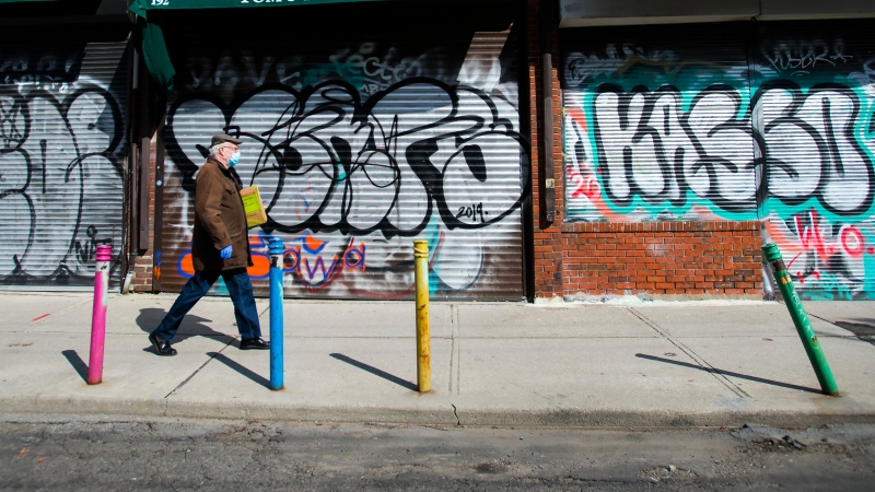 A lone person walks the empty streets in Kensington Market in Toronto on Wednesday, April 15, 2020. THE CANADIAN PRESS/Nathan Denette