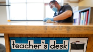 A custodian cleans a teacher's desk in a classroom at Brubaker Elementary School, Wednesday, July 8, 2020, in Des Moines, Iowa. (AP Photo/Charlie Neibergall)