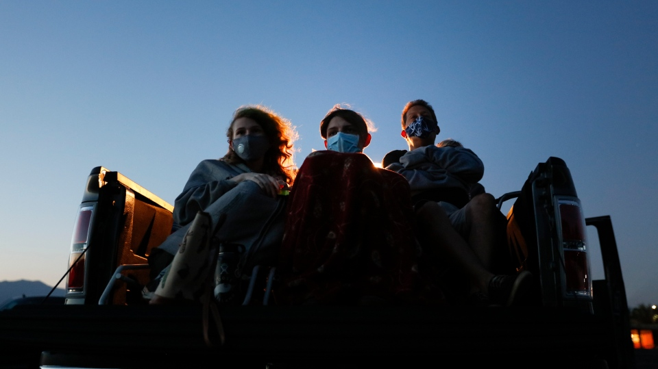 Moviegoers wear masks while watching a movie from a truck bed at Mission Tiki drive-in theater in Montclair, Calif., Thursday, May 28, 2020. (AP Photo/Jae C. Hong)