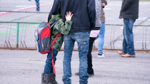 A boy hugs his father as he waits to be called to enter the schoolyard the Marie-Derome School in Saint-Jean-sur-Richelieu, Que. on Monday, May 11, 2020.  THE CANADIAN PRESS/Paul Chiasson