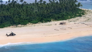 "In this photo provided by the Australian Defence Force, an Australian Army helicopter lands on Pikelot Island in the Federated States of Micronesia, where three men were found, Sunday, Aug. 2, 2020, safe and healthy after missing for three days. The men were missing in the Micronesia archipelago east of the Philippines for nearly three days when their ""SOS"" sign was spotted by searchers on Australian and U.S. aircraft, the Australian defense department said. (Australian Defence Force via AP)"