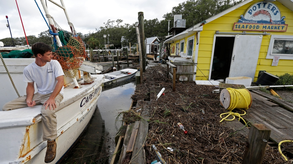Royce Potter, a fifth generation seafood fisherman, surveys the damage to his business, Potter's Seafood Market, following the effects of Hurricane Isaias in Southport, N.C., Tuesday, Aug. 4, 2020. Potter rode the storm out on his docked boat. (AP Photo/Gerry Broome)