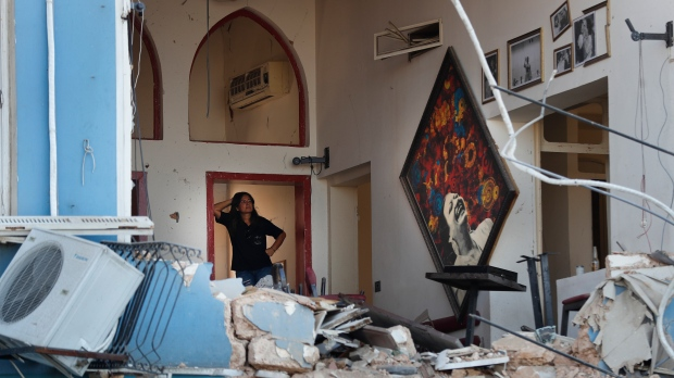 A woman stands inside a damaged restaurant a day after an explosion hit the seaport of Beirut, Lebanon, Wednesday, Aug. 5, 2020. Residents of Beirut stunned, sleepless and stoic emerged Wednesday from the aftermath of a catastrophic explosion searching for missing relatives, bandaging their wounds and retrieving what's left of their homes. (AP Photo/Hussein Malla)