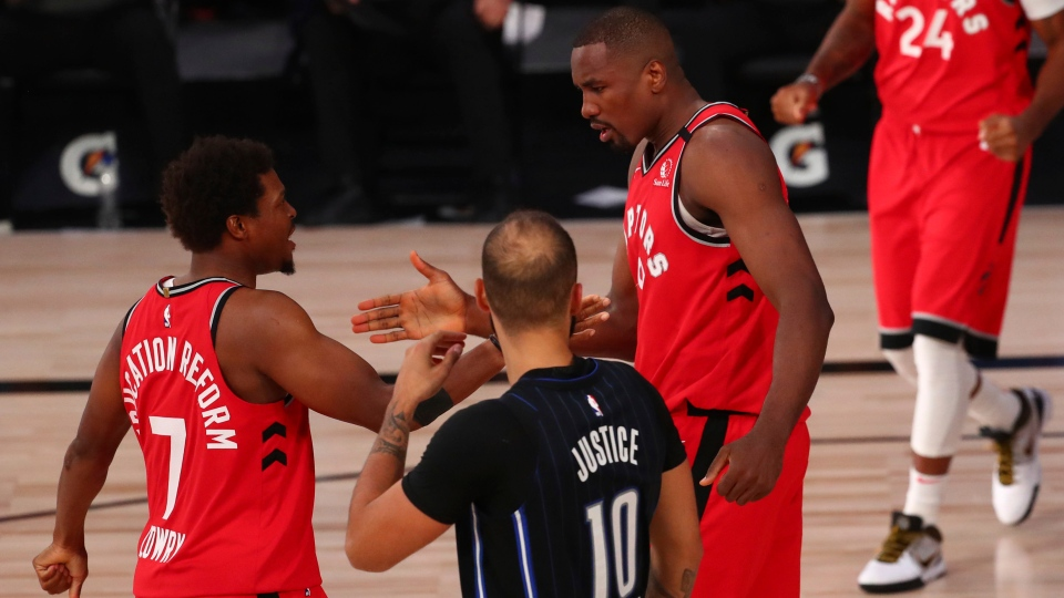 Toronto Raptors center Serge Ibaka (9) celebrates after scoring with guard Kyle Lowry (7) in the second half of an NBA basketball game Wednesday, Aug. 5, 2020, in Lake Buena Vista, Fla. (Kim Klement/Pool Photo via AP)
