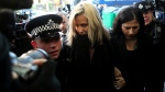 FILE - In this file photo dated Monday, Dec. 23, 2019, Love Island TV presenter Caroline Flack, centre, as she arrives at Highbury Magistrates' Court in London. (AP Photo/Petros Karadjias, FILE)