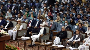 Afghan President Ashraf Ghani, center, wearing a protective face mask to help curb the spread of the coronavirus attends an Afghan Loya Jirga meeting in Kabul, Afghanistan, Friday, Aug. 7, 2020. The traditional council opened Friday in the Afghan capital to decide the release of a final 400 Taliban - the last hurdle to the start of negotiations between Kabul's political leadership and the Taliban in keeping with a peace deal the United States signed with the insurgent movement in February. (AP Photo/Rahmat Gul)