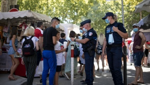 Municipal police give facemasks to pedestrians in Saint-Tropez, southern France, Saturday Aug 8, 2020. The glamorous French Riviera resort of Saint-Tropez is requiring face masks outdoors starting Saturday, threatening to sober the mood in a place renowned for high-end, free-wheeling summer beach parties. (AP Photo/Daniel Cole)