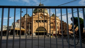 A cyclists passes an empty Flindres Street Station during lockdown due to the continuing spread of the coronavirus in Melbourne, Thursday, Aug. 6, 2020. Victoria state, Australia's coronavirus hot spot, announced on Monday that businesses will be closed and scaled down in a bid to curb the spread of the virus. (AP Photo/Andy Brownbill)
