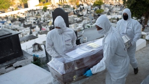 Cemetery workers in full protective gear carry the coffin containing the remains of Maria Pereira Domingos, 72, who died of the new coronavirus at the Nova Iguacu municipal cemetery in Nova Iguacu, Brazil, Friday, Aug. 7, 2020. COVID-19 deaths in Brazil are rapidly approaching 100,000. (AP Photo/Silvia Izquierdo)