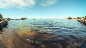 """In this photo provided by Grégoire Rouxel fuel is in the ocean leaking from a ship, rear right, that ran aground, Friday, Aug. 7, 2020, in Mauritius. The Indian Ocean island of Mauritius has declared a """"state of environmental emergency"""" after a Japanese-owned ship that ran aground offshore days ago began spilling tons of fuel. Prime Minister Pravind Jugnauth announced the development late Friday, Aug. 7, 2020, as satellite images showed a dark slick spreading near environmental areas the government called """"very sensitive."""" (@gregrouxel via AP)"""