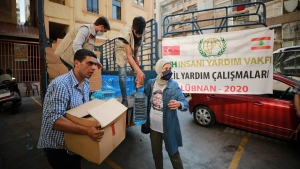 In this photo provided by Turkey's IHH humanitarian aid group, Turkish volunteers distribute food and water at the site of this week's massive explosion in the port of Beirut, Lebanon, Saturday, Aug. 8, 2020. Senior officials from Turkey, Middle East and Europe arrived in Lebanon Saturday in a show of solidarity with the tiny country that suffered a deadly blast this week which caused large-scale damage to the capital Beirut. (IHH via AP, Pool)