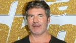 "In this Aug. 28, 2018, file photo, Simon Cowell arrives at the ""America's Got Talent"" Season 13 Week 3 red carpet at the Dolby Theatre in Los Angeles. Cowell broke his back Saturday, Aug. 8, 2020, while testing his new electric bicycle at his home in California. (Photo by Willy Sanjuan/Invision/AP, File)"